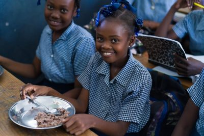 Schoolgirl in Haiti receiving WFP meal.